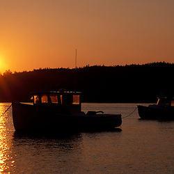 Pretty Marsh, ME. The sun sets over the harbor on Mt. Desert Island. Clouds. Boats.