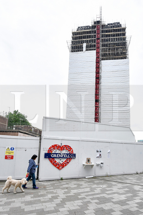 © Licensed to London News Pictures. 21/05/2018. LONDON, UK.  A member of the public walks by a hoarding decorated with a memorial heart to the victims of the Grenfell Tower fire tragedy.  Behind the hoarding, scaffolding currently covers the burned out shell of the Grenfell Tower in West London on the day that commemoration hearings begin in the Millennium Gloucester hotel.  Over the next nine days, friends and family will be paying tributes to the 72 victims killed by the fire in the building nearly one year ago.  Photo credit: Stephen Chung/LNP
