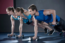Athletes doing push-ups in the gym by holding dumbbell, Bavaria, Germany