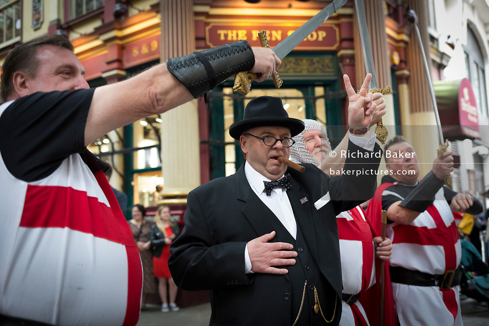 Winston Churchill impersonator, Derek Herbert gives a V for Victory after making the wartime leader's Battle of Britain speech in front of three knights and lunchtime drinkers on St George's Day in Leadenhall Market in the capital's financial district (aka The Square Mile), on 23rd April, City of London, England.