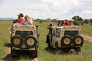 Tourist on a safari, looking at the wild life at Serengeti National Park is a region of grasslands and woodlands in United Republic of Tanzania