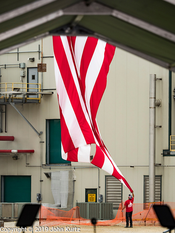 11 JUNE 2019 - COUNCIL BLUFFS, IOWA: A worker tries to wrangle a giant American flag that blew down in the wind before President Trump spoke at Southwest Iowa Renewable Energy Tuesday. President Trump visited Southwest Iowa Renewable Energy in Council Bluffs Tuesday to announce that his administration was relaxing rules on E15, an ethanol additive for gasoline. Iowa is one of the leading ethanol producers in the U.S. and Iowa corn farmers hope the administration's change in E15 rules will spur demand for corn.           PHOTO BY JACK KURTZ