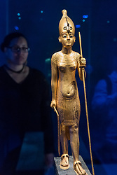 """© Licensed to London News Pictures. 01/11/2019. LONDON, UK. A woman views """"Wooden Statue of the King in the White Crown"""".  Preview of """"Tutankhamun, Treasures of the Golden Pharoah"""" at the Saatchi Gallery in Chelsea.  The exhibition celebrates the 100th year anniversary of the opening of Tutankhamun's tomb and displays 150 works in the largest collection of Tutankhamun's treasures ever to leave Egypt.  The show runs 2 November to 3 May 2020.  Photo credit: Stephen Chung/LNP"""