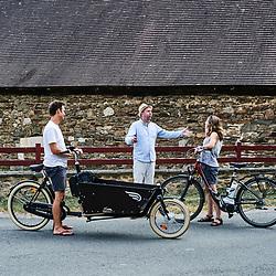 A locally-settled Dutch/US couple with their bikes, discussing with journalist Tim Hulse. Saint-Pierre-de-Frugie, France. July 12, 2019.<br /> Un couple americano-hollandais vivant sur place, avec leurs velos, en pleine discussion avec le journaliste Tim Hulse. Saint-Pierre-de-Frugie, France. 12 juillet 2019.
