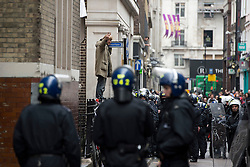 © London News Pictures. 11/06/2013. London, UK. An activists giving a peace gesture as Police waiting to raid a squat at abandoned police station on Beak Street, London which is being used by Anti-G8 activists as their headquarters ahead of a demonstration in central London today (Tues) The G8 Summit is due to take place in Norther Ireland early next week.  Photo credit: Ben Cawthra/LNP