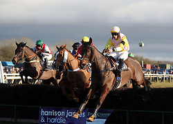 Horses jump a fence at the Cocklebarrow Point-to-Point horse race near Chippenham in Wiltshire.