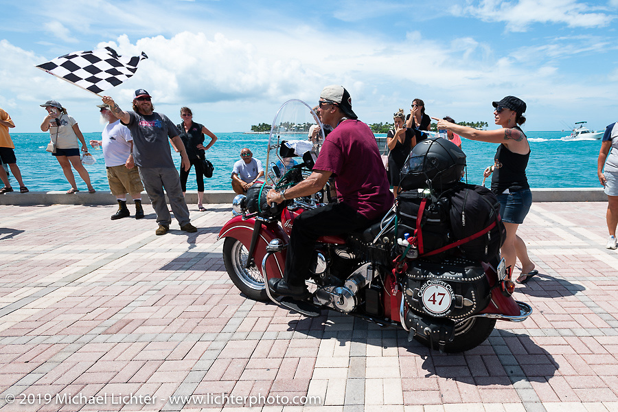 Kerry Patchett riding his 1947 Indian Chief over the finish line of the Cross Country Chase motorcycle endurance run from Sault Sainte Marie, MI to Key West, FL. (for vintage bikes from 1930-1948). The Grand Finish in Key West's Mallory Square after the 110 mile Stage-10 ride from Miami to Key West, FL and after covering 2,368 miles of the Cross Country Chase. Sunday, September 15, 2019. Photography ©2019 Michael Lichter.