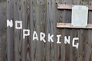 On a house's wooden garage gates the words No Parking have been painted by hand in white on wooden gates in a quiet suburban London street.