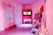 Little girl of four is dressed up in a fancy dress and applying make-up in a pink play room