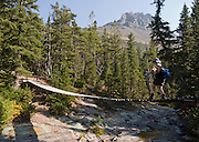 """A hiker crosses a swing bridge over Paradise Creek, on the trail to Cobalt Lake, in Glacier National Park, Montana, USA. Since 1932, Canada and USA have shared Waterton-Glacier International Peace Park, which UNESCO declared a World Heritage Site (1995) containing two Biosphere Reserves (1976). Rocks in the park are primarily sedimentary layers deposited in shallow seas over 1.6 billion to 800 million years ago. During the tectonic formation of the Rocky Mountains 170 million years ago, the Lewis Overthrust displaced these old rocks over newer Cretaceous age rocks. Glaciers carved spectacular U-shaped valleys and pyramidal peaks as recently as the Last Glacial Maximum (the last """"Ice Age"""" 25,000 to 13,000 years ago). Of the 150 glaciers existing in the mid 1800s, only 25 active glaciers remain in the park as of 2010, and all may disappear by 2020, say climate scientists."""