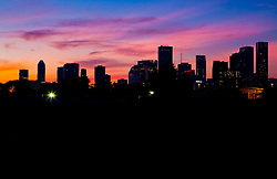 Colorful sunset behind the silhouette of the east downtown view of Houston, Texas skyline.