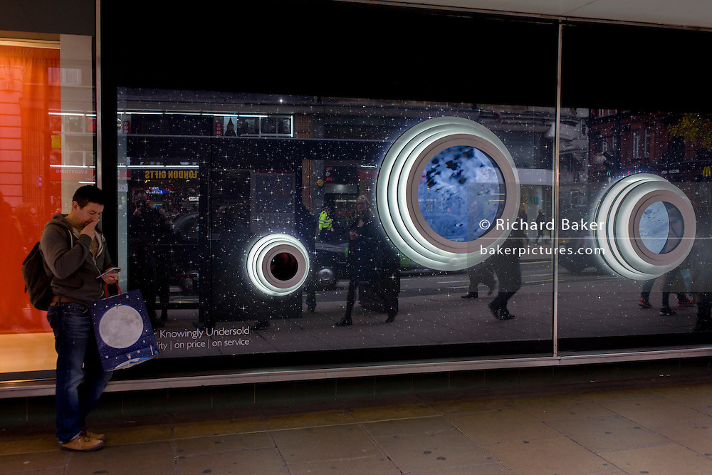Shopper and the circles of the John Lewis Man in the Moon Christmas theme in the window of the store's Oxford Street branch.