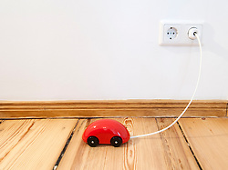 Concept of plug in electric cars showing Toy car  plugged into house mains electricity to recharge battery