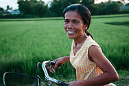 Hue, Vietnam - July 17, 2007: A woman rides a bicycle on a rural lane past rice fields near Hue.