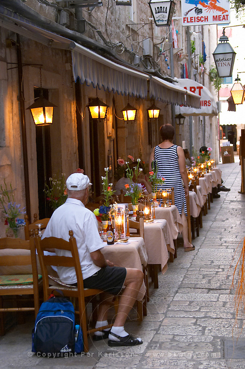 A man sitting waiting on the terrasse outside at a restaurant at dusk with lights lit Dubrovnik, old city. Dalmatian Coast, Croatia, Europe.