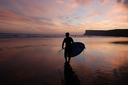 © Licensed to London News Pictures. <br /> 08/10/2014. <br /> <br /> Saltburn, United Kingdom<br /> <br /> Stand up paddle boarder Steve Bulmer walks toward the surf as the sky is dramatically lit up at dawn on Saltburn beach in Cleveland.<br /> <br /> Photo credit : Ian Forsyth/LNP