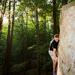 """A man bouldering in """"The Boulders"""" section of New Hampshire's Pawtuckaway State Park."""