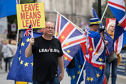 © Licensed to London News Pictures. 05/09/2018. London, UK. A pro-Brexit demonstrator passes a group of anti-Brexit demonstrators outside the Houses of Parliament, as two Brexit demonstrations happen simultaneously. Photo credit : Tom Nicholson/LNP