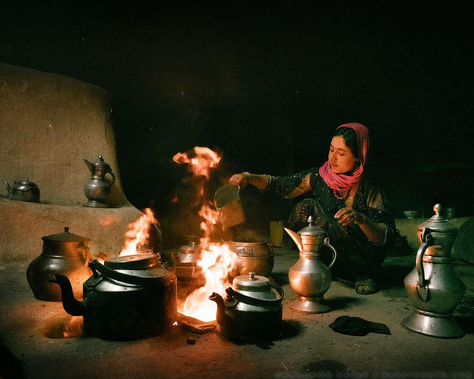 """Flames come out of  the """"dildung"""" also known as Tandoor (traditional cylindrical oven) while the daughter of Nida Khan prepares salty milk tea. Pots of water are constantly being heated up throughout the day and used for cooking, drinking or washing hands and face. The traditional life of the Wakhi people, in the Wakhan corridor, amongst the Pamir mountains."""