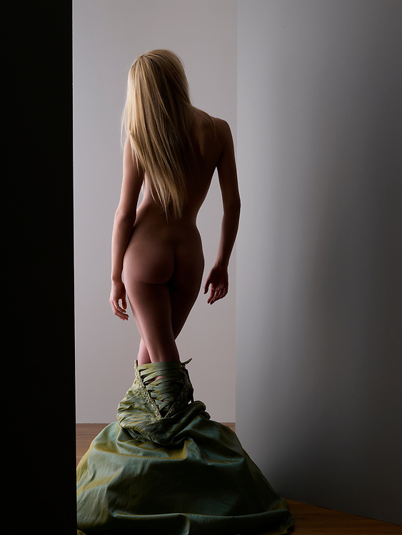 Nude woman whose dress has fallen to the floor, facing away from camera