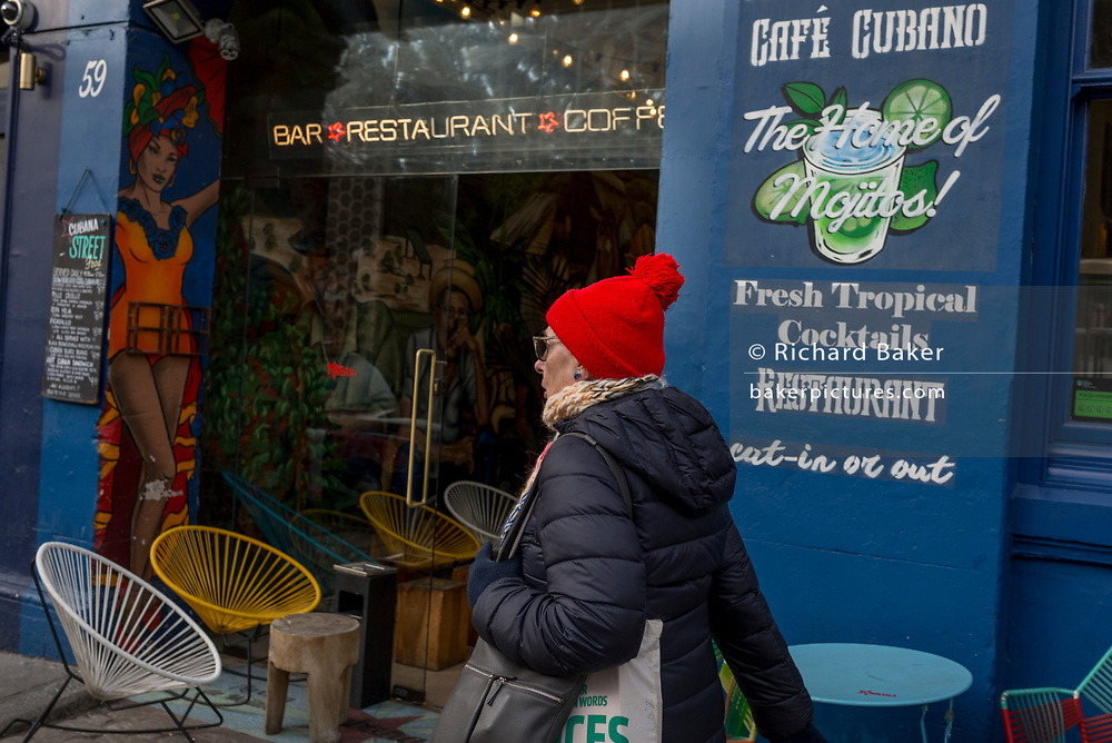 A lady walks past a Cuban cafe opposite Smithfield Market in Charterhouse Street, on 20th November 2019, in the City of London, England.