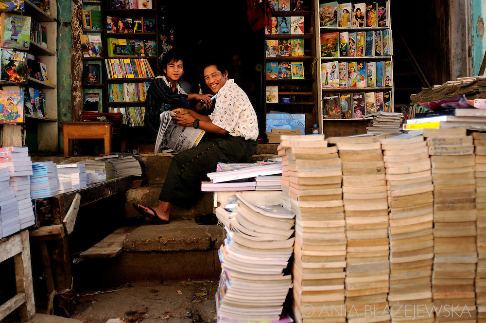 Myanmar/Burma. Smiling man and his son selling books in the bookshop situated in one of the streets of Yangon.