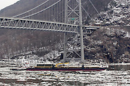 Bear Mountain, New York - A tugboat pushes barge south on the Hudson River by the Bear Mountain Bridge on Feb. 20, 2007.