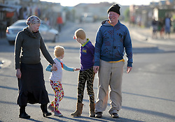 Cape Town- 180830 Nokwanda Tyongozi Linamandla Tyongozi Siphosethu Tyongozi and Themba Tyongozi from kuyasa Khayelitsha walking down the street from their house. The family are living with albinism. Albinism is a genetic condition. Primarily, albinism affects the hair eyes skin and vision The most common cause of albinism is an interruption in the functioning of the enzyme tyrosinase Picture:Ayanda Ndamane/ African News Agency ANA