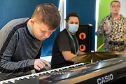 Support worker with service users during a music class. Client  - Allerton, an integrated social care, housing, and development company.