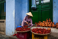 An old woman sells trinkets outside of a temple in Hoi An, Vietnam.