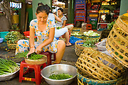 09 MARCH 2006 - HO CHI MINH CITY, VIETNAM: A woman chops vegetables for a restaurant on a street in Ho Chi Minh City (formerly Saigon) Vietnam. With an unofficial population of nearly 10 million (the official population is 6 million) business is done anywhere a businessperson can find space to do it, including the sidewalk. Photo by Jack Kurtz