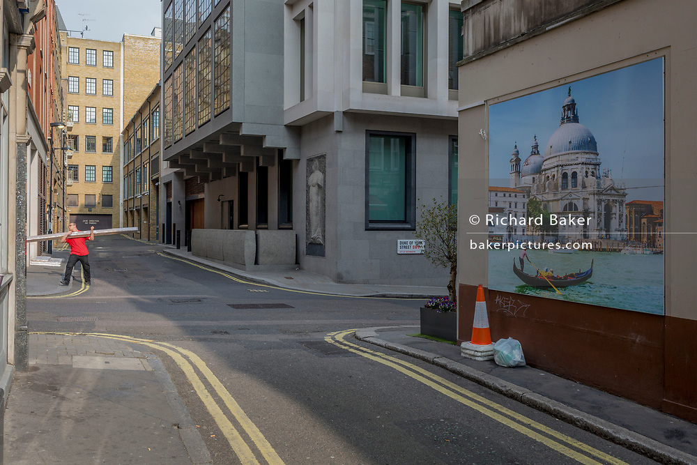 A red-shirted workman carries an awkward heavy load and a wall picture showing a gondolier and the church of Santa Maria della Salute church in Venice, on 16th March 2017, on the corner of Duke of York Street, in St james's, London, England.