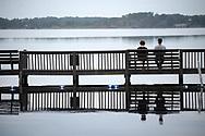 People soak in the scene of Lake Sheen from a dock at the Orange County Sportsmen's Association property in Orlando, Fla., Tuesday, Dec. 15, 2015. (Phelan M. Ebenhack via AP)