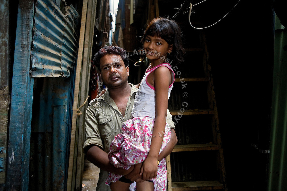 Rubina Ali, 9, the child actor playing the role of 'young Latika', the friend/lover of Jamal, protagonist of Slumdog Millionaire, the famous movie winner of 8 Oscar Academy Awards in December 2008, is portrayed in the arms of her father, Rafiq Qureshi, 33, on the streets near her uncle's house in the slum where she still lives with her family next to the train station of Bandra (East), Mumbai, India. Various promises were made to lift the two young actors (Azharuddin Ismail and Rubina Ali) from poverty and slum-life but as of the end of May 2009 anything is yet to happen. Rubina's house was recently demolished with no notice as it lay on land owned by the Maharashtra train authorities and she is now permanently living with her uncle's family in a home a stone-throw away in the same slum. Azharuddin's home too was demolished in the past two weeks, as it happens every year in his case, because the concrete walls were preventing local authorities to clear a drain passing right behind it. As usual, his father is looking into restoring the walls as soon as the work on the drain has been completed.
