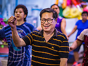 11 AUGUST 2016 - BANGKOK, THAILAND:   A man works out in an aerobics class in Pak Khlong Talat, better known as the Bangkok Flower Market. Public exercise classes are common throughout Thailand. Most of the participants in the exercise class in the Bangkok flower market are older adults, although the class is open to everyone.       PHOTO BY JACK KURTZ