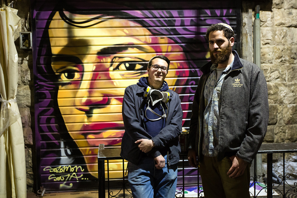 Artist Solomon Souza (L) and Berel Hahn (R), who came up with the idea to paint over shutters at the Jerusalem market, pose for a photograph in front of Souza's latest street art piece depicting Israeli-Arab news anchor Lucy Aharish which he spray-painted over a closed shutter at the Mahane Yehuda Market, often called 'The Shuk' in Jerusalem, Israel, on February 24, 2016.