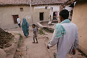 IND.MWdrv04.081.x..Bachau Yadav, 42, walks past cow dung patties drying in his village. They are used for cooking fuel. Ahraura Village, Uttar Pradesh, India. Revisit with the family, 2004. He and his family were India's participants in Material World: A Global Family Portrait, 1994 (pages: 64-65), for which they took all of their possessions out of their house for a family-and-possessions-portrait..
