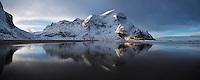 Winter reflection of Storskiva and surrounding mountains on Bunes beach, Moskenesøy, Lofoten Islands, Norway