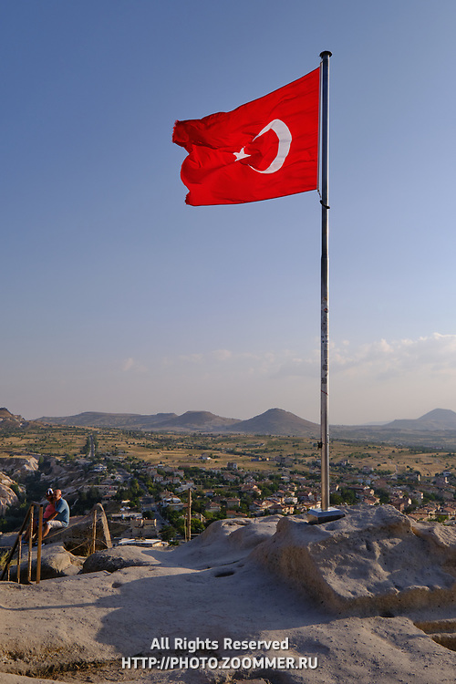 Big turkish flag on top of the ancient Uchisar castle in Cappadocia, Turkey