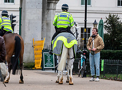 © Licensed to London News Pictures. 21/01/2021. London, UK. Mounted police in Hyde Park speak to a member of the public today. Police continue to patrol parks across the capital while members of the public wrapped up against the wind and enjoy a walk during lockdown. Today, Prime Minister Boris Johnson warned that it was too early to know if Covid-19 restrictions would be lifted in spring or even summers as infections continue to spread throughout out the capital and the rest of the UK. Photo credit: Alex Lentati/LNP