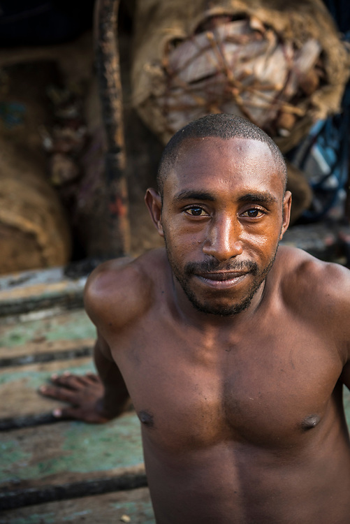 Portrait of a crewman of a small boat that carries copra (background) from islands of Madang Province to the mainland of Papua New Guinea