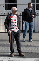 © Licensed to London News Pictures. 06/07/2016. London, UK.  Protestor Michael Culver wearing a t-shirt listing the number of dead in the Iraq war looks on as the convoy of Former Prime Minister Tony Blair leaves his home. The Iraq Inquiry, Chaired by Sir John Chilcot, is finally being published today, six years after it was started. The long awaited report into the Iraq war, the run-up to the conflict in Iraq, the military action and its aftermath is 2.6 million words long.  Photo credit: Peter Macdiarmid/LNP