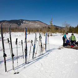 A group of cross-country skiers takes a lunch break on the Pleasant River Trail between West Branch Pond Camps and Little Lyford Pond Camps near Greenville, Maine.  Baker Mountain is in the distance.