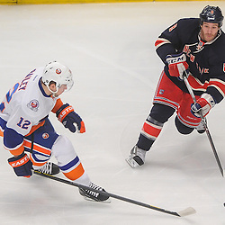New York Rangers right wing Brandon Prust (8) passes the puck away from New York Islanders center Josh Bailey (12) during first period NHL action between the New York Islanders and the New York Rangers at Madison Square Garden in New York, N.Y.