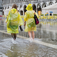 VENICE, ITALY - JUNE 07:  Tourists in St Mark's Square seems to enjoy the unusual high water that has flooded the square this afernooni on June 7, 2011 in Venice, Italy. Thunderstorms and heavy rain have hit Venice causing an out season high tide of 90 cm flooding St Mark's square.
