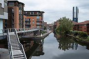 Bride and groom have their wedding pictures taken beside the Birmingham Canal Old Line in the city centre on 9th July 2021 in Birmingham, United Kingdom. This is a popular spot for photographs and is near the Birmingham Registry Office.
