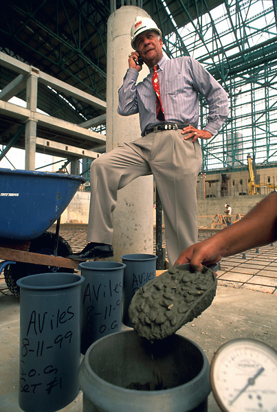 Stock photo of Dionel Aviles, founder and president of Aviles Engineering Corporation, takes a call while a workman prepares concrete samples.