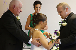 Bride who has cerebral palsy being helped by her grandfather at wedding ceremony with groom and registrar.
