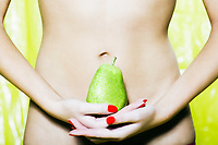 caucasian woman holding a pear abdomen digestion concept studio on yellow background