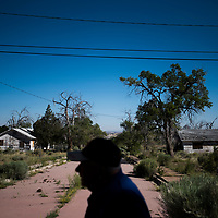 """Martin Link stands among abandoned homes along a street at Fort Wingate on Wednesday. """"Standing on the site where these things happened is a visual kind of history lesson,"""" Link says. He believes the fort should be considered a national monument, and protected as such."""